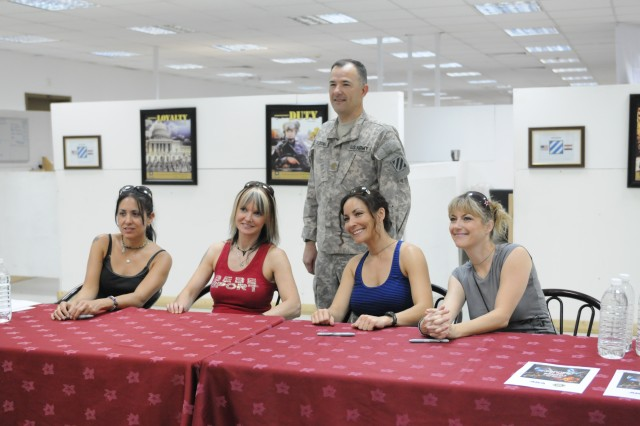 """Major Andrew Fletcher, Knowledge Management Officer, G-3, poses behind the Hammer of the Broads, an all-female tribute band honoring the music of Led Zeppelin, during a """"meet and greet"""" at Task Force Marne headquarters, Sept. 8. The band was a COB Speicher for a concert later that night at the Main Gym."""