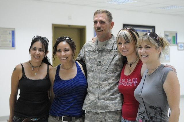 """Staff Sergeant Caray Sharpe, G-3 Air, poses with the Hammer of the Broads, an all-female tribute band honoring the music of Led Zeppelin, during a """"meet and greet"""" at Task Force Marne headquarters, Sept. 8. The band was a COB Speicher for a concert later that night at the Main Gym."""