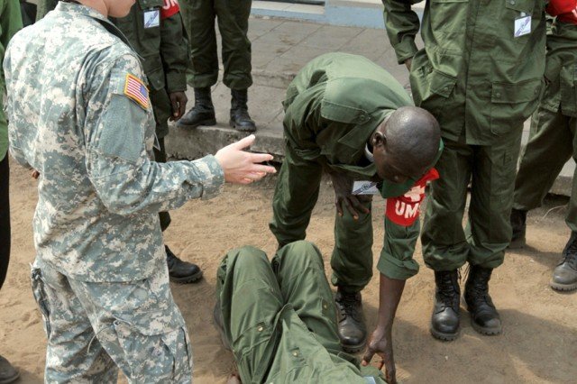 Spc. Brooke Glatt of Bismarck, N.D., teaches members of the Armed Forces of the Democratic Republic of Congo how to evaluate a casualty. Glatt, a member of the 814th Army Medical Support Company based in Bismarck, is in the DRC as part of MEDFLAG 10, a joint military training exercise between the U.S. military and FARDC soldiers to enhance emergency response capabilities in the region.