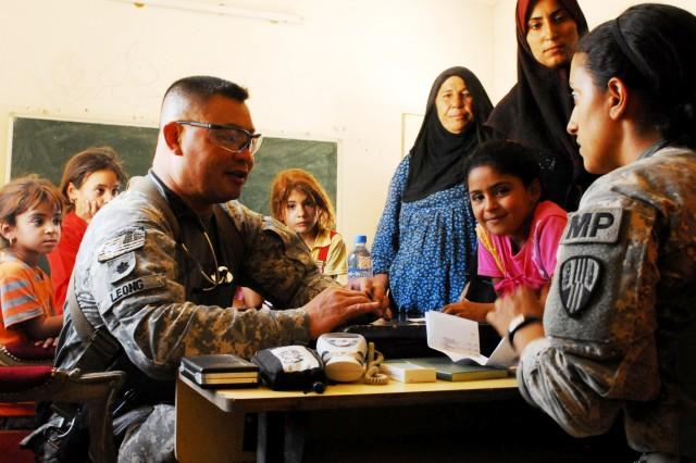 Lt. Col. Jonathan Leong, left, a surgeon assigned to 3rd Battalion, 15th Infantry Regiment, 4th Advise and Assist Brigade, 3rd Infantry Division, United States Division-Center, treats women and children at a free clinic during an Iraqi Security Forces-led medical engagement Sept. 7 in Karmah, Iraq. Spc. Latifa Gaisi, right, a Soldier with the 442nd Military Police Company, helps translate. U.S. forces partnered with the ISF to host the event.