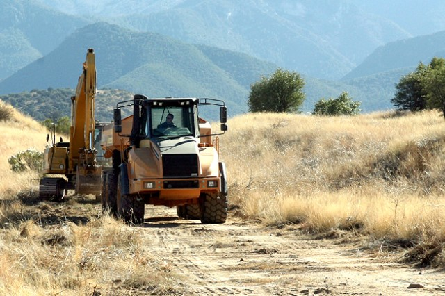 "Heavy equipment makes its way to an articulating dump as part of the process of clearing range 12 of scrap metal to make way for ""greener"" targets that will assist with the fort's environmental protection efforts. This is an example of one project range control worked on to enhance the environment while providing a more realistic training environment."