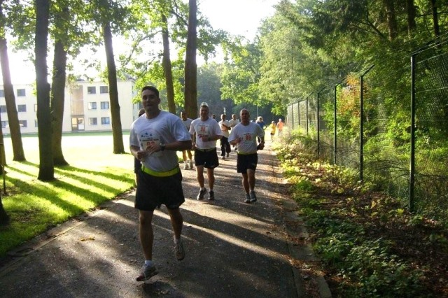 USAG Schinnen's Staff Sgt. Brandon Elliott takes the lead, with Sgt. Craig Kosobucki and Spc. Floyd Cyderman following closely behind in the 9/11 Mile Freedom Run that took place on SHAPE, Sept. 11.