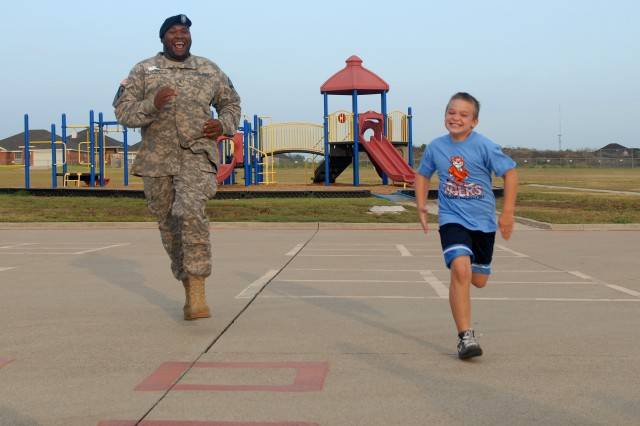 KILLEEN, Texas - RJ Riley (right), 9, a third grader at Trimmier Elementary School, races Sgt. Dillard Hughes, from San Jose, Calif., a generator mechanic with Company E, 4th Attack Reconnaissance Battalion, 227th Aviation Regiment, 1st Air Cavalry Brigade, 1st Cavalry Division, before the start of the schools 9/11 remembrance ceremony, Sept. 10. Nearly 40 Soldiers visited Trimmier Elementary School to help with the morning's events which included a flag folding ceremony and the annual Freedom Walk.