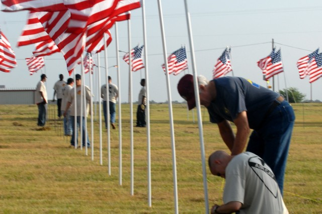 KILLEEN, Texas-A Soldier (kneeling) from 1st Air Cavalry Brigade, 1st Cavalry Division, and a member of the Patriot Guard help put up American flags for the Field of Honor display, part of the American Veterans Traveling Tribute, at the Killeen Civic and Conference Center, Sept. 9.