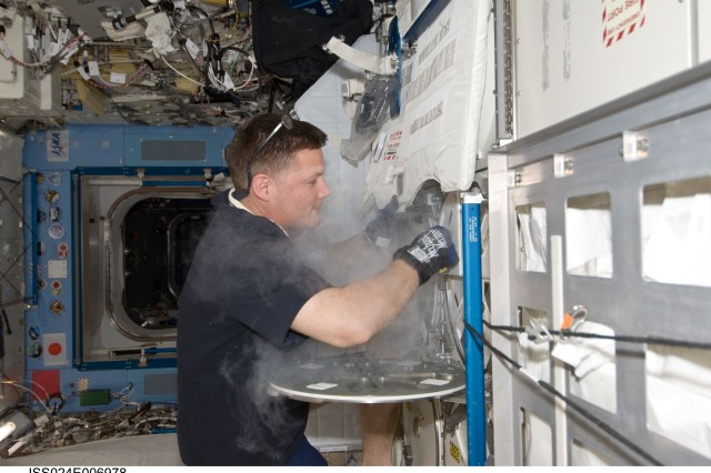 NASA astronaut Doug Wheelock, Expedition 24 flight engineer, services the Minus Eighty Laboratory Freezer for ISS (MELFI-1) in the Kibo laboratory of the International Space Station.