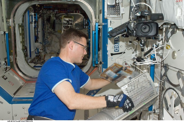 NASA astronaut Doug Wheelock, Expedition 24 flight engineer, services the Minus Eighty Laboratory Freezer for ISS-2 (MELFI-2) in the Destiny laboratory of the International Space Station.
