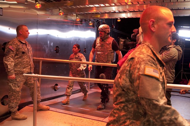 Geoff Howe, center, walks on a treadmill in the arctic chamber at NSSC wearing a helmet and body armor as Sgt. Maj. John Poff looks on.