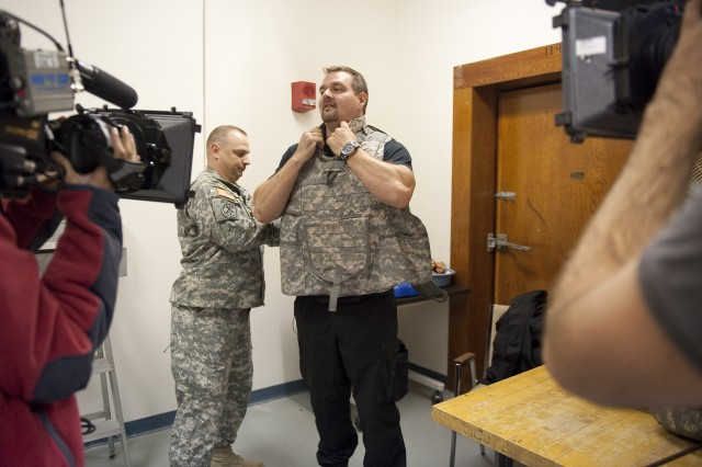 Geoff Howe gets help with body armor from Sgt. Maj. John Poff at the climatic chamber during filming of episode for Discovery Channel.