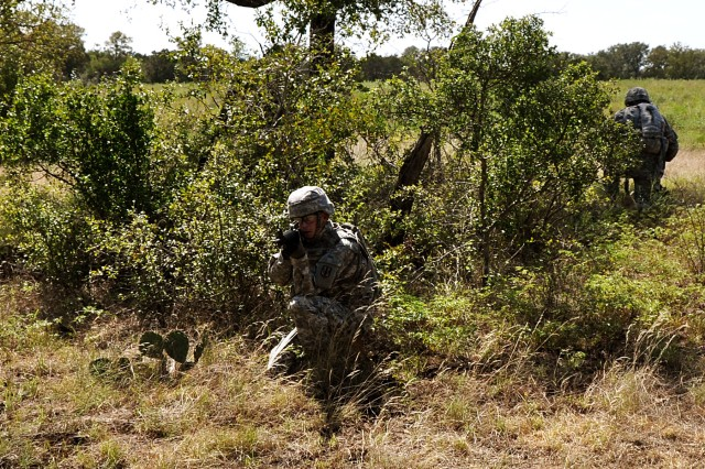"""FORT HOOD, Texas-Pfc. Blake Essex, from Carmel, Ind., a radar repair specialist with Battery A, 26th Field Artillery Regiment, 41st Fires Brigade, pulls security while a team clears out a local village of """"insurgents"""" during a cordon and search training mission on North Fort Hood, Texas, Sept. 10. The training also allowed for a California National Guard unit to train on its tactical training procedures."""