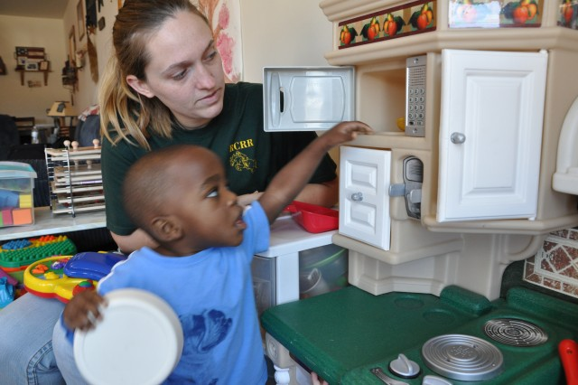 Kasey Tanner, a Fort Jackson Family Child Care provider, shows 15-month-old Elija Kirkland how to play with an educational toy Tuesday.