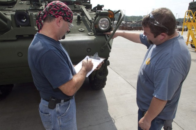 Ronald Concord and Judd Gedgoudas perform final checks on a Stryker at Anniston Army Depot before presenting it to the Defense Contract Management Agency for final inspection.