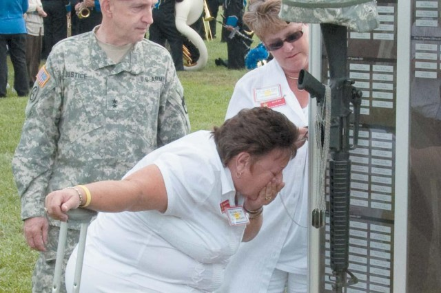 Aberdeen Proving Ground commander, Maj. Gen. Nick G. Justice, left, looks on as Gold Star Mother Jane Craig of Earleville, center, kisses the ID tags of her son, Cpl. Brandon M. Craig who was killed in Iraq in 2007. Beverly Fabri, of Chestertown, the mother of Pvt. Bryan N. Spry, searches for her son's tags on the Fallen Heroes Monument after the 9/11 Remembrance Ceremony at Fanshaw Field Sept. 10.