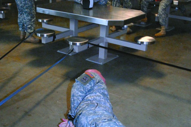 Sgt. James Bennett, 165th Military Police Company, 705th MP Internment and Resettlement Battalion, portrays a hostage taken by inmates who have barricaded themselves in the dining facility during a training scenario Sept. 9 at the Joint Regional Correctional Facility, Fort Leavenworth, Kan. Soldiers who will be working in the facility trained on emergency action plans for a variety of scenarios while executing normal daily operations. The JRCF begins receiving actual inmates in October.