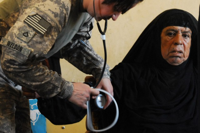 Private First Class Charity Weldon, a medic with Company C, 703rd Brigade Support Battalion, 4th Advise and Assist Brigade, United States Division-Center, checks vitals of a Karmah, Iraq, resident during a combined medical engagement between U.S. forces and Iraq Security Forces, Sept. 7.