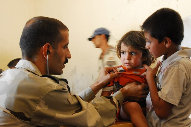An Iraqi Army doctor examines a child during an Iraqi Security Forces-led combined medical engagement and humanitarian aid mission. U.S. forces partnered with the ISF to host the event, Sept. 7.