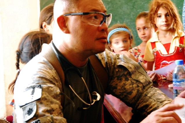 Lieutenant Colonel Jonathan Leong (left), surgeon assigned to the 3rd Battalion, 15th Infantry Regiment, 4th Advise and Assist Brigade, 3rd Infantry Division, United States Division - Center, treats women and children at a free clinic during an Iraqi Security Forces-led medical engagement Sept. 7 in Karmah, Iraq, as Spc. Latifa Gaisi, a Soldier with the 442nd Military Police Company, helps translate. U.S. forces partnered with the ISF to host the event.