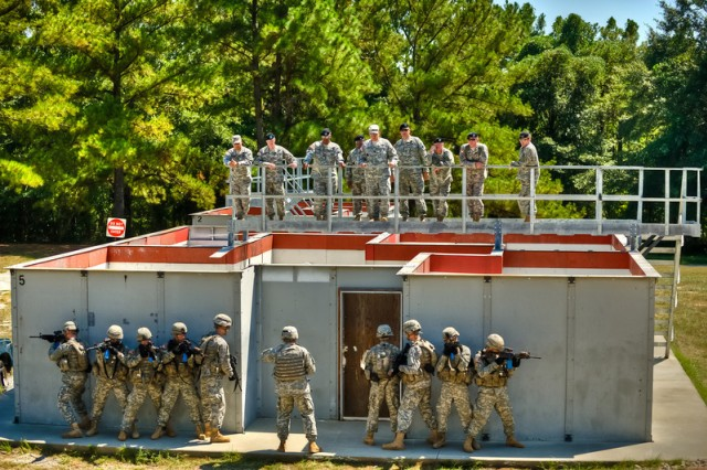 Soldiers prepare to enter a building while command sergeants major watch from above