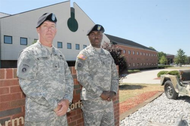 Lt. Col. Mark A. Westbrook,Transportation School assistant commandant, and Sgt. Maj. Joseph A. Clarida Jr., school sergeant major, pose in front of the school headquarters at Fort Lee, Va.
