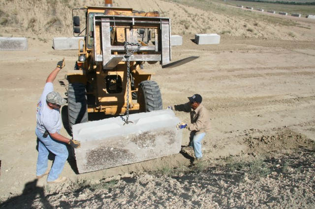 FORT CARSON, Colo.-Pat Wolf, left, and Mario Dalangin, target systems workers, Range Control Division, guide a protective block into place in a Bradley misfire pit on Range 111 Sept. 10.