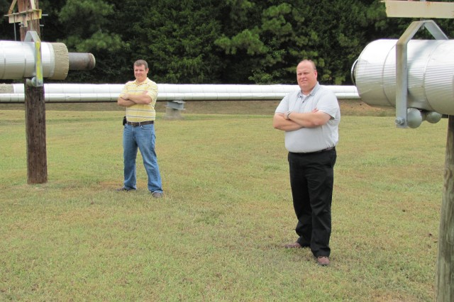 Energy manager Mark Smith, in foreground, and co-worker Patrick Holmes stand within part of the four miles of decommissioned steam lines. New natural gas lines were installed through a utility energy savings contract with TVA.