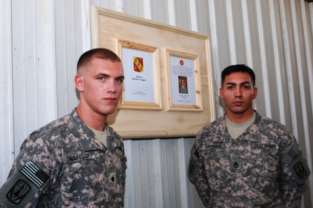 Spc. Devin Swanson, a Soldier in Battery A, 5th Battalion, 5th Air Defense Artillery Regiment, left, and Staff Sgt. Joshua Medina, also with 5-5 ADA, stand beside the plaque to commemorate the dedication of the Combat Stress Clinic Sept. 10. The clinic is used to help Soldiers deal with stress of a combat zone.