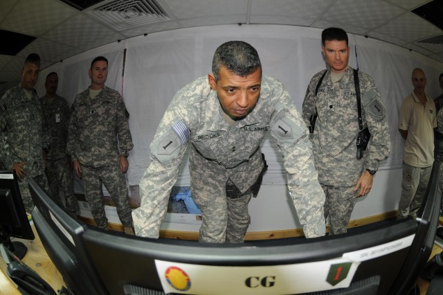 Maj. Gen. Vincent Brooks, commanding general of the 1st Infantry Division and United States Division-South, starts up the Command Post of the Future Battle Command 10 as Lt. Col. Richard Hornstein, left, the product manager for Tactical Battle Command, and Lt. Col. Juan Vazquez, right, the 1st Infantry Division communications officer, look on at the 1st Inf. Div. headquarters in Basra, Iraq, Sept. 11. The CPOF BC10 provides commanders with near real-time information about anything going on in their area of operations.
