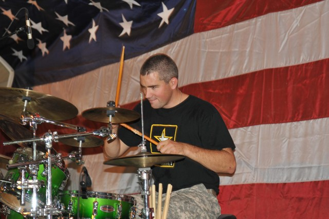 Staff Sgt. Glenn Robertson, drummer for the Volunteers of the U.S. Army Field Band and a native of Spencer, Mass., plays at the Basra Resiliency Campus Sept. 16. Robertson and the rest of the Volunteers are the first component of the U.S. Army Field Band to perform in a combat zone.