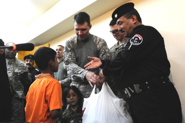 U.S. Army Capt. Page Brooks, a chaplain with the Louisiana National Guard, and Maj. Gen. Sabah Hassan Al-Shelby, commander of the Baghdad Police Headquarters, hand out bags of clothing, toys and hygiene items to the orphans of fallen Iraqi Police officers in Baghdad, Sept. 14, 2010.