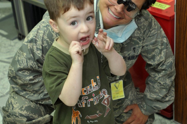 The son of an embassy worker in Kinshasa, Democratic Republic of the Congo, shows Air Force Lt. Col. Jacqueline Garcia-Castellanos of Miami that he knows how to floss his teeth Sept. 12. Garcia-Castellanos a reservist with the 482nd Aeromedical Dental Squadron, Homestead Air Reserve Base, Fla., is in the DRC as part of MEDFLAG 10, a joint training exercise with the U.S. and FARDC militaries focusing on humanitarian and civil assistance.  U