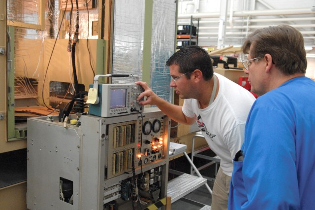 Chris Luongo, left, and Ray Reiss, electronics integrated systems mechanics, align a threat transmitter for an AN/MST-T1 (V) Miniaturized Multiple Threat Emitter System at Tobyhanna Army Depot.
