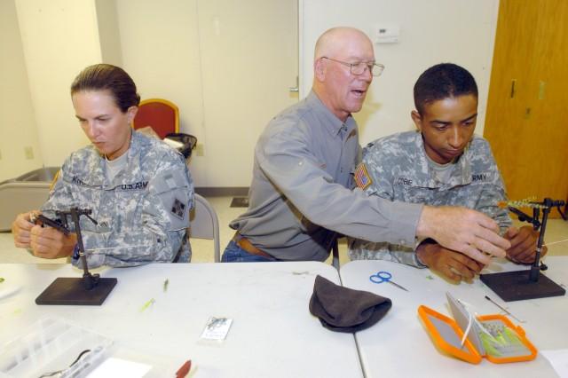 "PHWFF Fort Hood coordinator Bill Adams tutors Spec. Jason Coberly, B Company, 2nd Battalion, in the art of fly tying, while Pvt.2 Jennifer Knott  wraps her Aca,!A""stealth bomber.Aca,!A?"