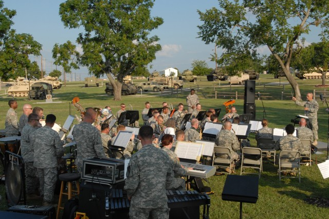 """FORT HOOD, Texas - Chief Warrant Officer 2 Michael Moore (far right), from Austin, commander and band master of the 1st Cavalry Division Band, conducts the band while they play """"Preserve the Legend March,"""" written by Peter Giles, at the 1st Cavalry Division Museum, here, Sept. 14.  The song is the only march ever written for a museum, said Steve Draper, museum director for the 1st Cavalry Division Museum.  The band continued the Preserve the Legend Concerts for an audience of Soldiers, families and local community."""