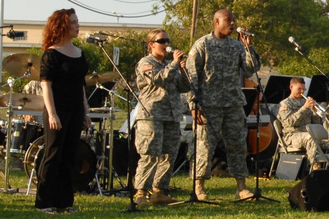 """FORT HOOD, Texas - April Hayes (left) from Westerville, Ohio, a guest singer from Vive Les Arts Theatre, sings the song """"Wicked,"""" written by Stephen Schwartz, along with Spc. Breanna Lemons (center) from Conroe, Texas, a clarinet player for the 1st Cavalry Division Band, and Sgt. Christopher Fairley from Moss Point, Miss., a vocalist for the 1st Cav. Div. Band, at the 1st Cavalry Division Museum, here, Sept. 14."""