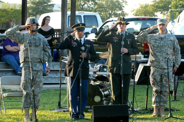 """FORT HOOD, Texas - From left to right, Spc. William Eiler, from Palm Beach, Fla.; Spc. Steven Fulir, from Boston; Spc. William Shepherd, from Nashville; and Spc. William Rabun, from Colorado Springs, all band members in the 1st Cavalry Division Band, salute after reciting the """"Soldier's Creed"""" while the band played """"Fantasy on Army Strong,"""" written by Mark Isham. This was part of the band's Preserve the Legend Concert series at the 1st Cavalry Division Museum, Sept. 14."""