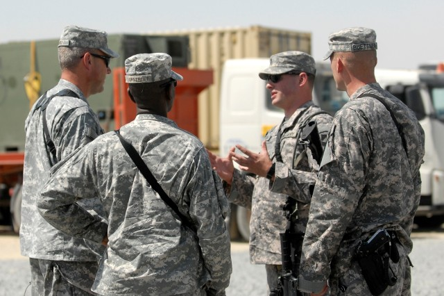 CAMP BUEHRING, Kuwait - First Lt. Michael Sexton (gesturing), a platoon leader assigned to 2nd Battalion, 12th Cavalry Regiment, 4th Brigade Combat Team, 1st Cavalry Division, speaks with brigade commander, Col. Brian Winski (far left), at the Port of Kuwait, Sept. 18.  Sexton, a native of Buffalo, N. Y., prepared the brigade's equipment for transportation from Kuwait to Iraq for their mission supporting Operation New Dawn.