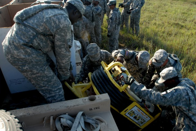FORT HOOD, Texas - Soldiers from Company E, 1st Attack Reconnaissance Battalion, 227th Aviation Regiment, 1st Air Cavalry Brigade, 1st Cavalry Division, work together to unload fire extinguishing equipment on the forward arming and refueling point, here, Sept. 15.