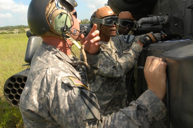 FORT HOOD, Texas - Sergeant Roderick Rhodes (center), a squad leader from Dallas, trains Spc. Samba Sima (back), from Mali, West Africa to fuel an AH-64D Apache attack helicopter while Sgt. Sean McConnell (front), a pad chief from Columbus, Ohio, talks to one of the pilots over his radio at a forward arming and refueling point, Sept. 15.