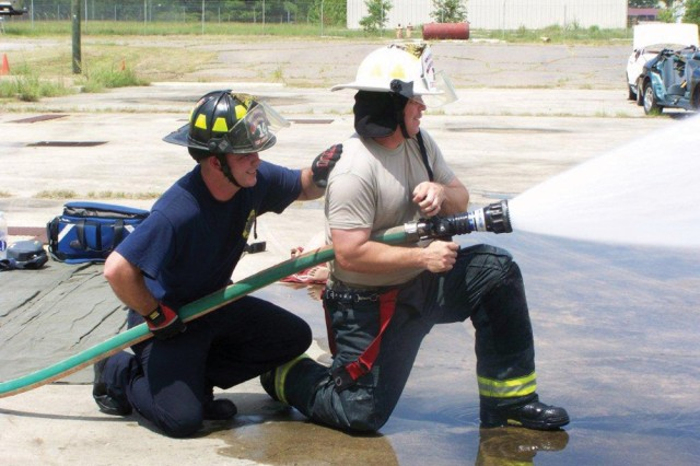 Lead from the front. Col. Glenn Kennedy, Fort Gordon garrison commander, is instructed on the proper use of a fire hose by an installation firefighter.