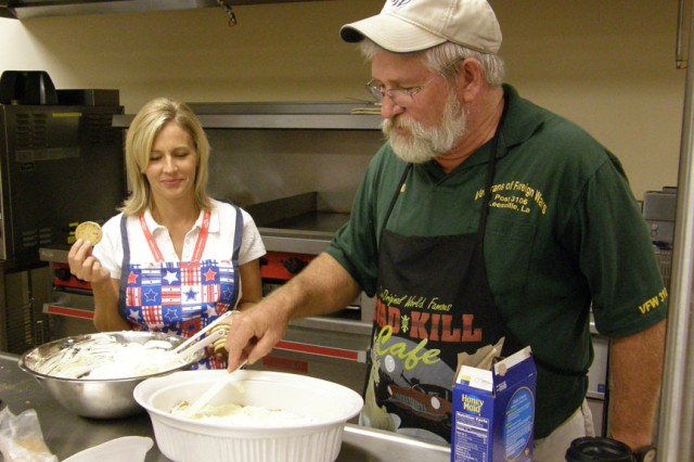 "FORT POLK, La. -- Alison Hedges waits patiently to crumble some cookies into the decadent dessert Steve Humphries is cooking with the help of spouses during his ""Cajun cooking: Delightfully Sinful"" class at the Joint Readiness Training Center and Fort Polk's 2010 Woman's Conference."