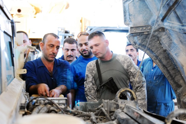 Spc. Henry Moss, a mechanic with 4th Advise and Assist Brigade, 3rd Infantry Division, discusses repair of a humvee engine with mechanics from the Iraqi Ministry of Defense.