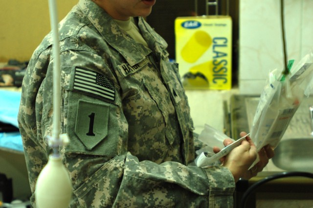 Sgt. Jessie Harter, a Soldier working at the Enhanced Combat Aviation Brigade, 1st Infantry Division, consolidated level-two clinic on Camp Taji, Iraq, prepares supplies in one of the clinicAca,!a,,cs trauma rooms.