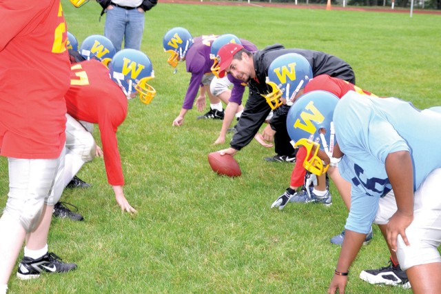 Child, Youth and School Services' Brad Hagan (red ball cap) shows Wiesbaden 12-14-year-old players some defensive moves during practice.