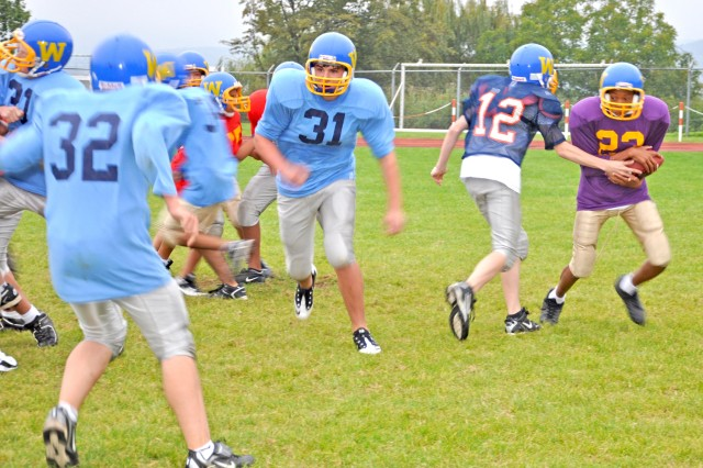 Wiesbaden 12-14-year-old players work on a hand-off play during Child, Youth and School Services tackle football practice.