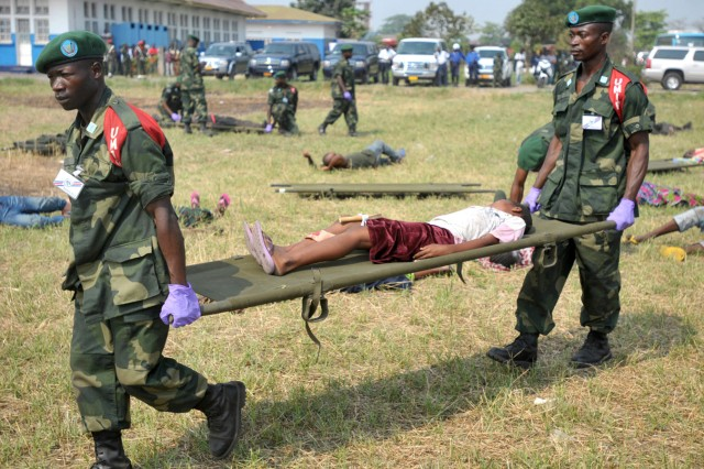 """Two soldiers with the Armed Forces of the Democratic Republic of the Congo quick reaction force (UMIR) carry a mock patient on a litter to the triage tent during a simulated mass casualty bus crash exercise Sept. 16 in Kinshasa, Democratic Republic of the Congo.   """""""