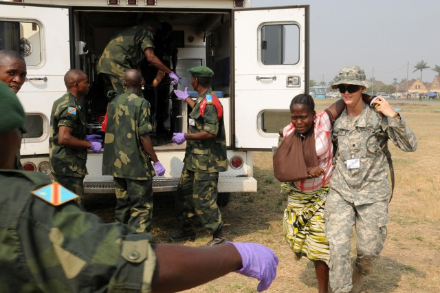 """Spc. Kerry Thompson, a combat medic with the North Dakota National Guard's 814th Army Support Medical Company based in Bismarck, carries a simulated injury patient to the waiting hands of an Armed Forces of the Democratic Republic of the Congo soldier Sept. 17. in Kinshasa, Democratic Republic of the Congo.   """""""
