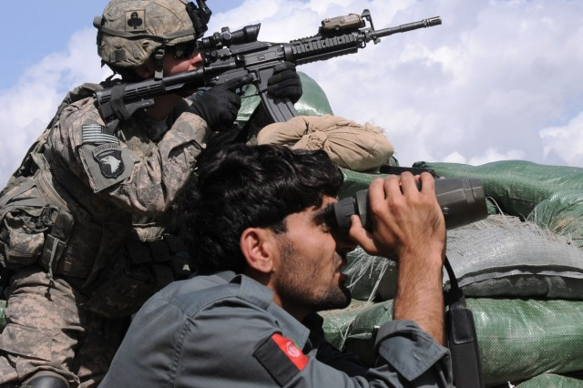 Pfc. Ryan L. Carson, a member of the Intelligence Support Team with Company A, 1st Battalion, 327th Infantry Regiment, and an Afghan police officer search the nearby hillside just prior to a more than three-hour firefight at the Shege East Afghan National Police Checkpoint Sept. 18.
