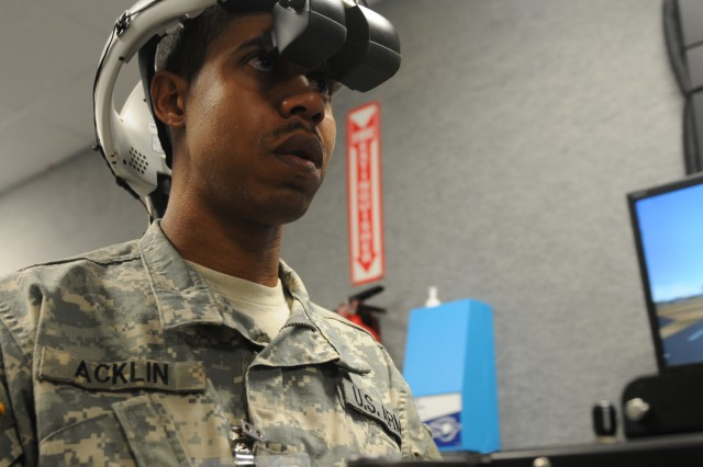 """Staff Sgt. Marcus Acklin, 689th Engineer Company, mans the mock .50 caliber machine gun on a Medium Mine Protected Vehicle """"JERRV"""" Virtual Route Clearance Simulator. The image in the monitor to Acklin's right is a representation of what he sees in the view finder of the head hardness he's wearing.  Acklin and 14 other Army Reservists from the 689th validated upgrades to the """"JERRV,"""" the Mine Protected Clearance Vehicle """"Buffalo,""""  the Medium Mine Protected Vehicle """"RG31,""""  the Vehicular Mounted Mine Detector """"Husky,"""" and the Man Transportable Robotic Systems """"Talon."""" The upgrades included an Afghanistan database, seat shakers, additional Improvised Explosive Devices, additional markers and colors, and a detonation cord for the """"Talon."""""""