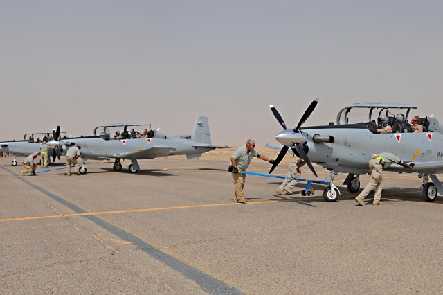 """Crew members secure proper parking positions for three T6 Texan II aircraft after their land at Contingency Operating Base Speicher, near Tikrit, Iraq, Sept. 21. The aircraft, which is used for training purposes by Iraqi pilot students, arrived with two other T6 model aircraft and is an addition to the eight T6 models currently at COB Speicher, with four more arriving in November, equaling a total number of 15 T6 models."""""""