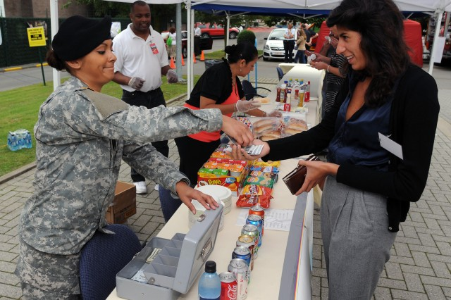 Sgt. Lizette Diaz, (left), the Patient Administrator at the SHAPE Brussels Health Clinic, was one of several Soldiers from the U.S. Army Garrison Brussels Better Opportunities for Single Soldiers chapter who sold food at the garrison's annual Information Fair.
