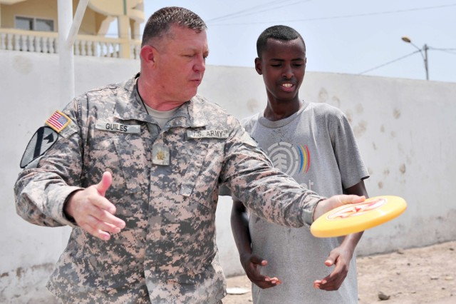 U.S. Army Maj. Michael Guiles, 418th Civil Affairs Battalion team leader, teaches a Djiboutian youth how to throw a Frisbee Sept. 13, 2010.